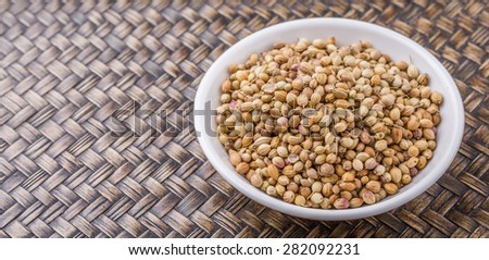 Coriander seeds in white bowl over wicker background