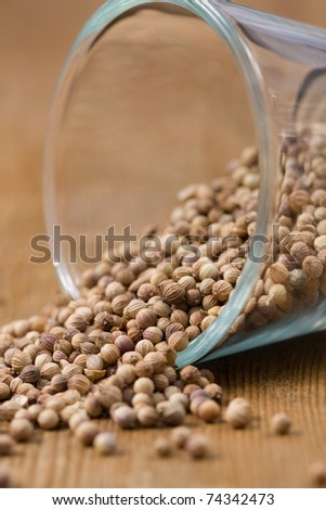 Coriander seeds spilling from a glass bowl