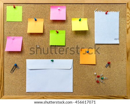 Cork board for notes in office with envelope color sticky blocks, staples, sheet. - stock photo