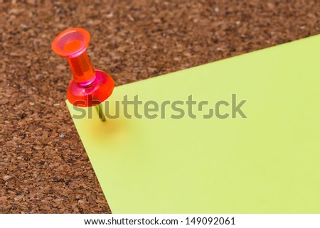cork board with a plastic pin and a blank note - stock photo