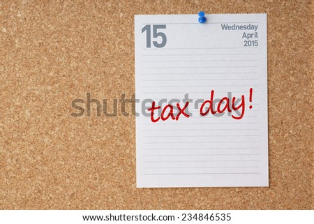"""Cork board with April 15 calendar page and """"tax day"""" reminder.  - stock photo"""
