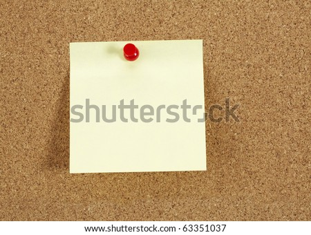 Cork board with blank yellow paper note - stock photo