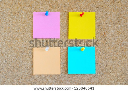 Cork board with multiple colorful post-it - stock photo