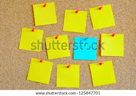 Cork board with multiple yellow and one cyan post-it - stock photo