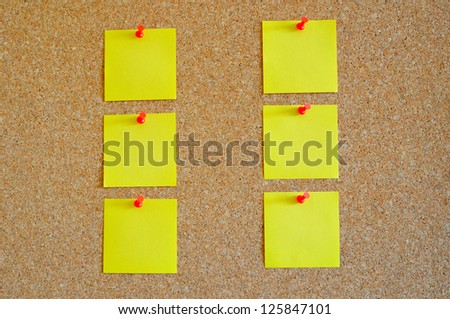 Cork board with multiple yellow post-it - stock photo