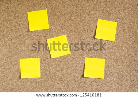 Cork board with yellow sticky notes - stock photo