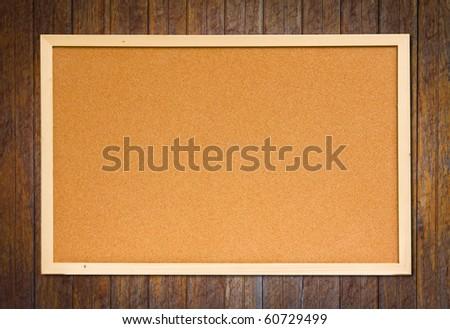cork bulletin board on wood wall - stock photo