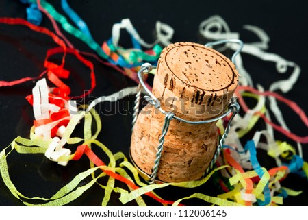 Cork in the middle of confetti against a black background - stock photo