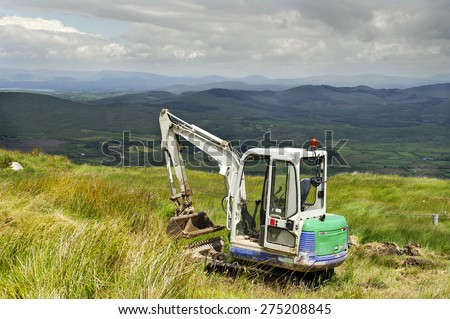 CORK,IRELAND - MARCH 30: Mini Digger in the Mountains West Cork on March 30, 2014 in Cork, Ireland. - stock photo