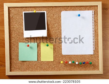 Cork message board with various paper notes. - stock photo
