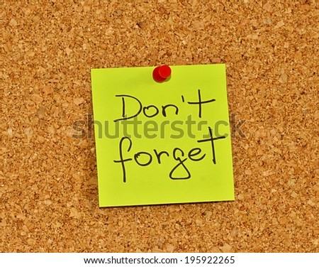 Cork notice board with one yellow sticky note pad with text please do not forget - stock photo