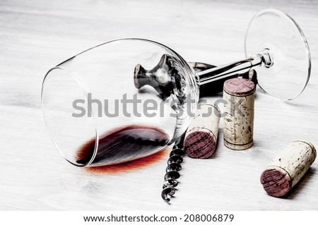 Corks, corkscrew and wine glass on a wooden table - stock photo