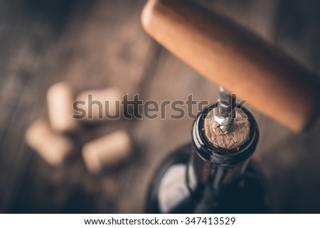 Corkscrew and bottle of wine on the board - stock photo