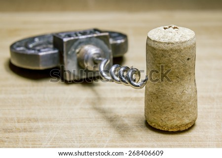 Corkscrew and Cork from wine on a wooden surface,macro - stock photo