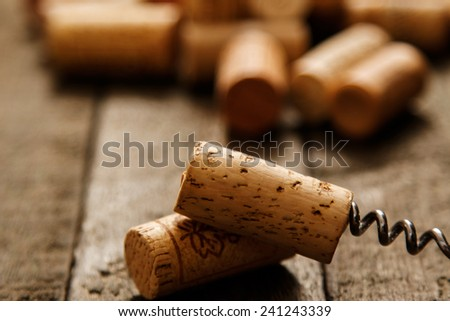 Corkscrew and wine corks on wooden surface - stock photo