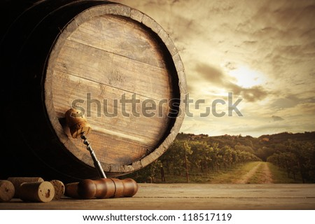 corkscrew and wooden barrel, vineyard on background - stock photo