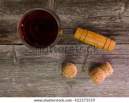 Corkscrew, cork and wine lie on a wooden table - stock photo