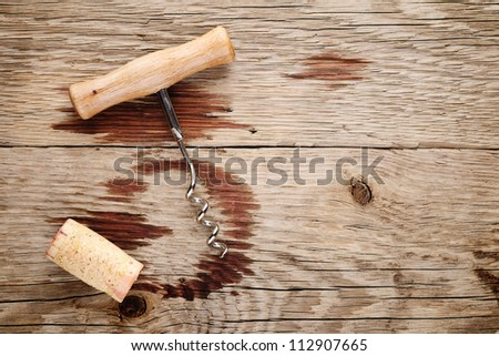 Corkscrew, cork and wine stains on wooden background - stock photo
