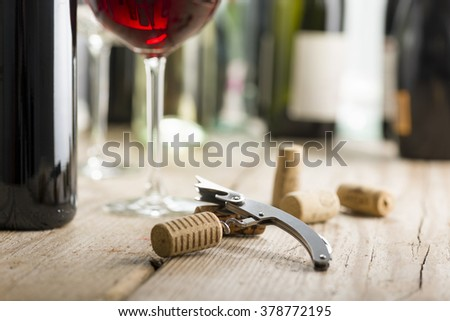 corkscrew with cork inserted near wine glass and bottle - stock photo