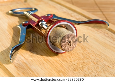 Corkscrew with stopper on board - stock photo