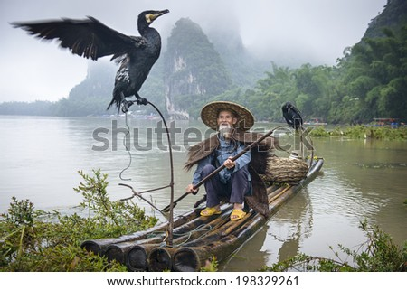 Cormorant fisherman and his bird on the Li River in Yangshuo, Guangxi, China. - stock photo