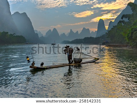 Cormorant fisherman stands on the ancient bamboo boat - The Li River, Xingping, China - stock photo