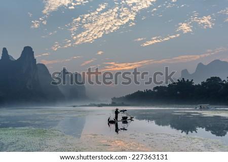 Cormorant fisherman stands on traditional bamboo boats at sunrise - The Li River, Xingping, China - stock photo