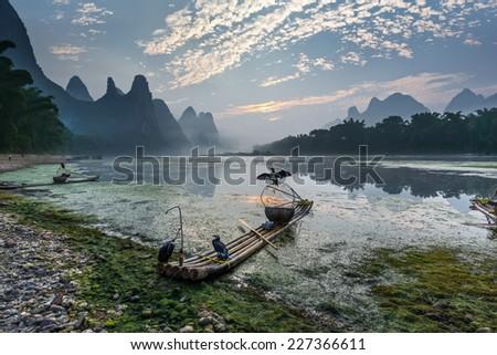 Cormorants sitting on the ancient bamboo boats at dawn - The Li River, Xingping, China - stock photo