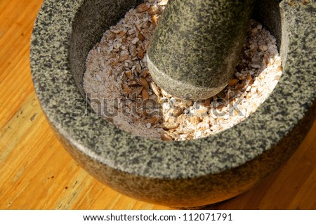 Corn being grinded with mortar and pestle made of stone to produce flour. This method has been in use for many thousand years. - stock photo