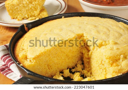 Corn bread in a cast iron skillet with a bowl of chili in the background - stock photo