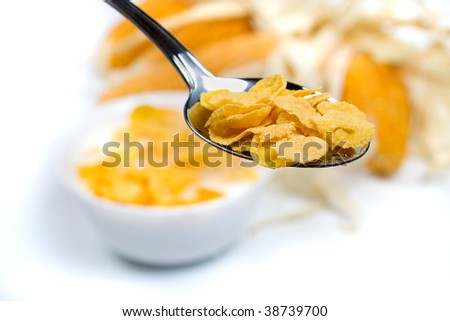 Corn cereals in a spoon over white background - stock photo