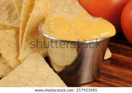 Corn chips and nacho cheese sauce closeup, shallow depth of field - stock photo