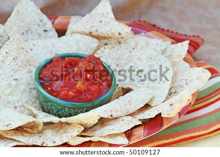 Corn chips and salsa on a colorful platter. - stock photo