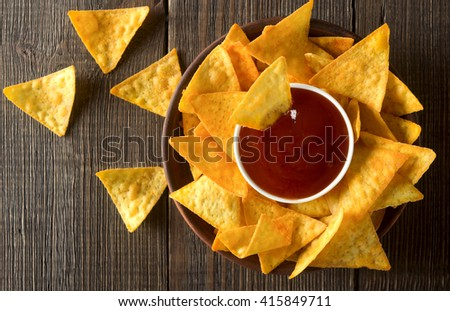 Corn chips  nachos with salsa sauce on a wooden table. - stock photo