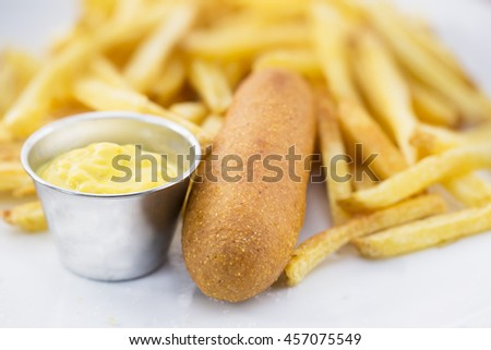 Corn dog with fries and mustard