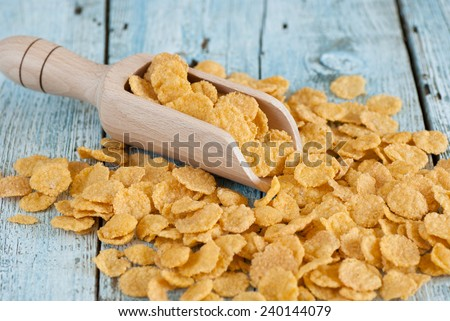 Corn flakes in scoop on old wooden table