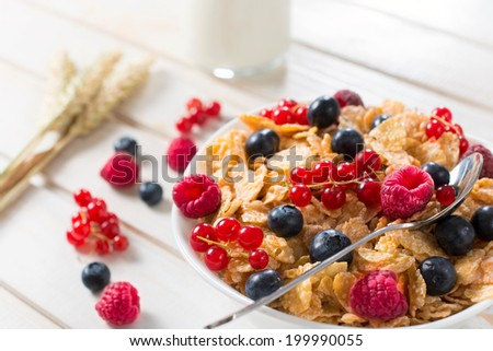 Corn flakes with berry fruit in the bowl.Selective focus in the middle of bowl - stock photo