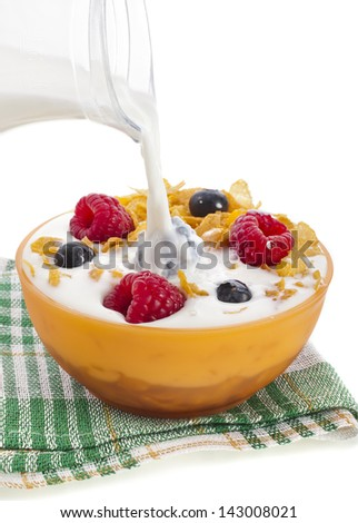 corn flakes with fresh berries and pouring splash milk isolated on white background