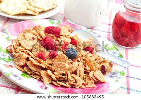 Corn flakes with fresh fruits, milk, jam and cookies - stock photo