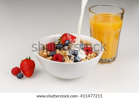 Corn flakes with pouring milk and Orange juice