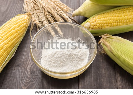 Corn flour and corn on wooden table. - stock photo