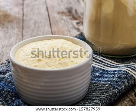 corn flour on wooden background  - stock photo
