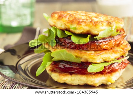 Corn fritters stacked with roasted tomatoes and arugula - stock photo