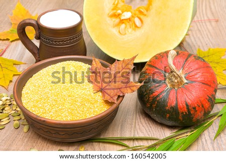 corn grits, ripe pumpkin and milk in a clay mug on wooden boards. horizontal photo. - stock photo