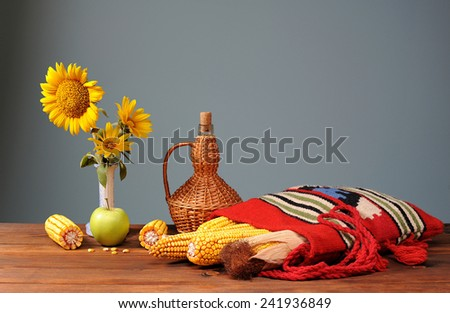 Corn in ethnic bags, sunflower and apple on the table - stock photo