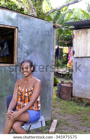 CORN ISLAND, NICARAGUA-NOV. 16:  A woman proudly sits in front of her new sheet metal house, called a zinc house, in Corn Island, Nicaragua on  November 16, 2015. - stock photo