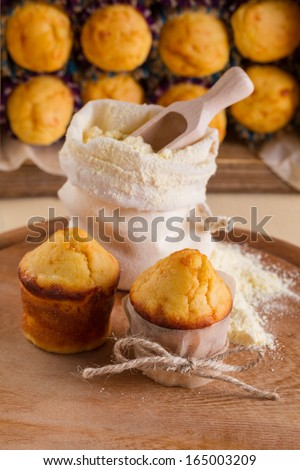 Corn muffins and a bag of flour on background muffin packaging - stock photo