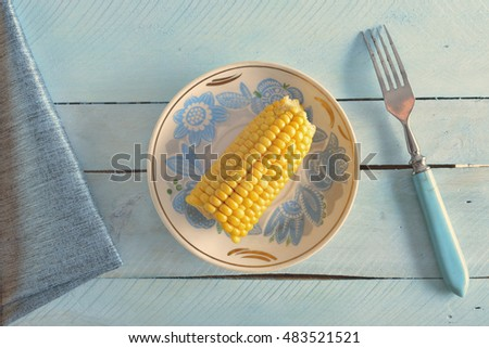 corn on the plate with fork and napkin on blue wooden background (incorrect white balance)