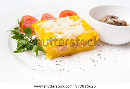 Corn polenta with tomato and mushroom sauce - stock photo