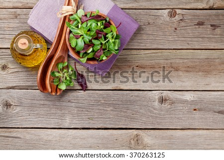 Corn salad leaves, utensils and olive oil on wooden table. Valerianella locusta. Top view with copy space - stock photo